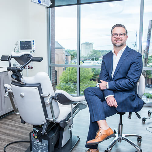 Dr. Adamiak sitting on a chair on a dental treatment room