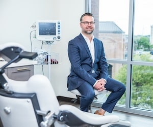 Dr. Mark Adamiak sitting on a chair next to modern dental technology