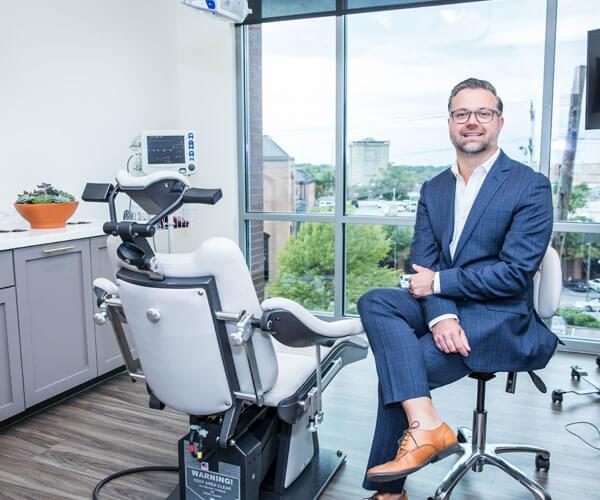Dr. Mark Adamiak sitting on a chair in his treatment room