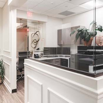 Our front desk office area with a glass screen and modern desk
