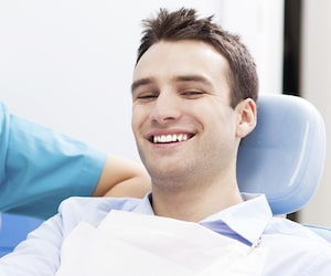 Young man with short brown hair laying a dental treatment chair