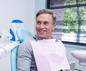 Grey-haired man sitting in a dental chair and smiling