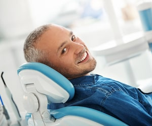 Man laying in a treatment chair wearing a denim shirt and looking back while smiling