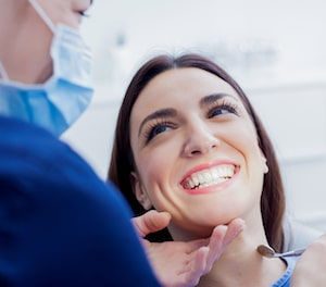 Woman with dark brown hair sitting in dental chair and smiling at the dentist